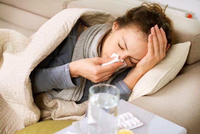 Grippe : femme qui se mouche