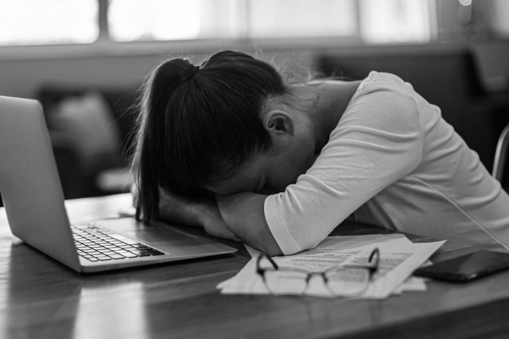 Depréssion : Femme fatiguée et stressée par son travail, devant son ordinateur à la maison.